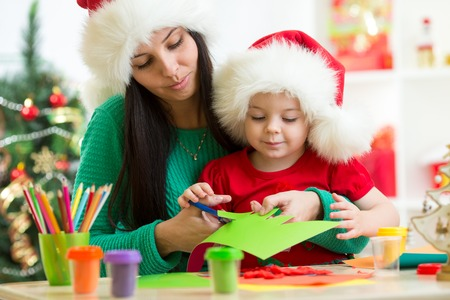 hat new year happy new year festive: Mother and child cut christmas tree from paper preparing to holiday Stock Photo