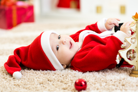 carpet: Happy Smiling baby lying on back wearing Christmas Santa hat and suit