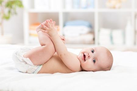 bebisar: söt baby barn liten flicka liggande på rygg och hålla benen Stockfoto