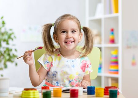 day care center: smiling kid girl painting with paintbrush at home or day care center Stock Photo
