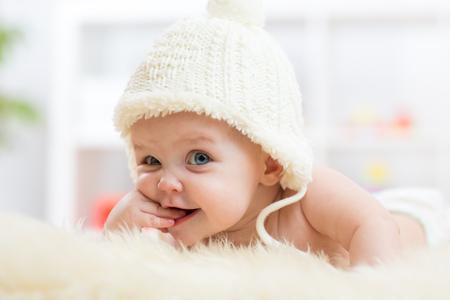 嬰兒: 可愛的小女嬰尋找到相機和weared的白帽子。