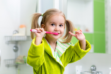 Smiling kid child girl brushing teeth in bathroom