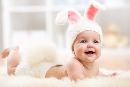 rabbits: Smiling cute baby child in rabbit costume lying on fur in nursery Stock Photo