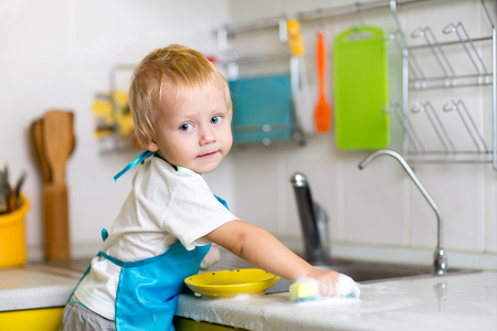 domestic: Child boy washing dishes in a domestic kitchen
