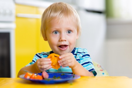 eating food: Cute child little boy eats healthy food vegetables Stock Photo