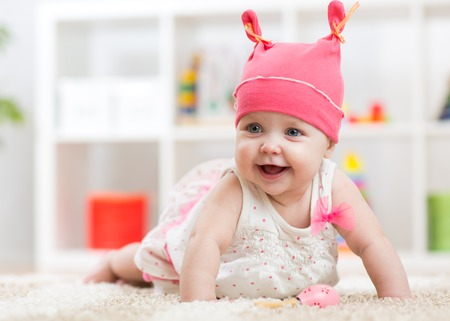 nursery room: Smiling baby child crawling on nursery room floor