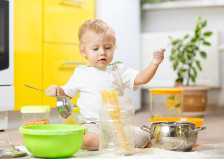 smeared baby: Child little boy playing with kitchenware and foodstuffs in kitchen Stock Photo