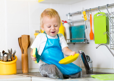 Kid child boy washing dishes and having fun in the kitchen