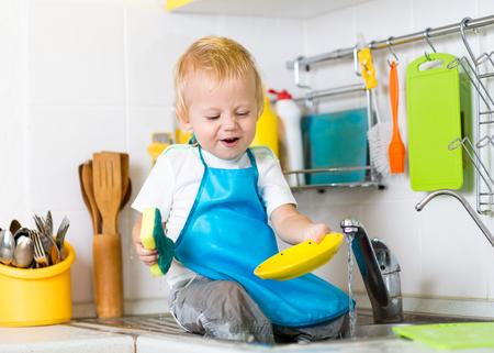 lavandose las manos: platos de lavado de Ni�os el ni�o chico y que se divierte en la cocina Foto de archivo