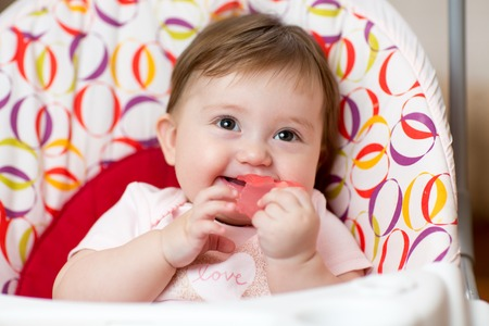 teething: Cute baby child with teething ring sitting in craddle
