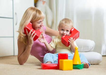 communicaton: cute mother and kid boy role playing together indoor