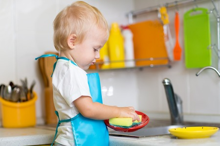 Cute child boy 2 years old washing dishes in kitchen