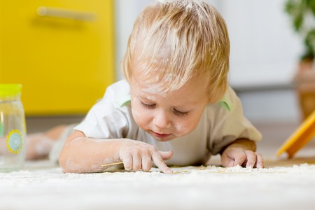 messy kitchen: Little boy child laying on very messy kitchen floor, covered in white baking flour Stock Photo