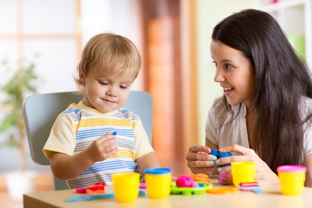 child kid boy and mother play colorful clay toy at nursery or kindergarten Stock Photo