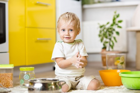groat: Playful child boy with kitchenware and foodstuffs on floor in kitchen