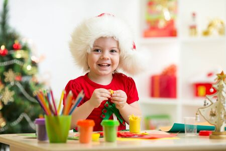 creation: Kid child girl making by hands x-mas decorations