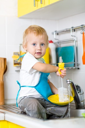 lavar trastes: platos de lavado lindo muchacho niño y que se divierte en la cocina
