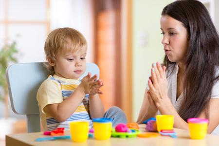 kind Junge und seine Mutter spielen bunten Spielzeug Ton im Kindergarten oder Kindergarten