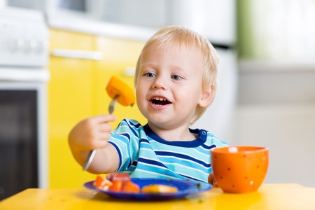 child food: Cute child little boy eating healthy food in kitchen Stock Photo