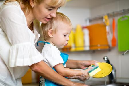 wash dishes: Madre enseña a su hijo pequeño niño hijo a lavarse en marcha Foto de archivo