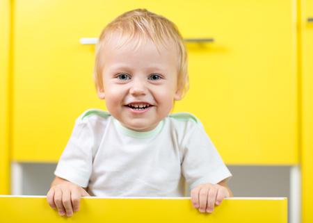 tallboy: Kid boy sitting inside yellow opened kitchen box Stock Photo