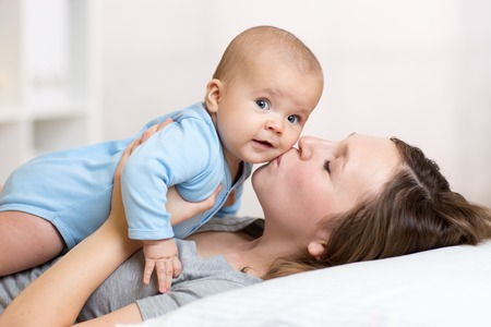 in kiss: Cute mother kissing baby lying on bed in nursery Stock Photo