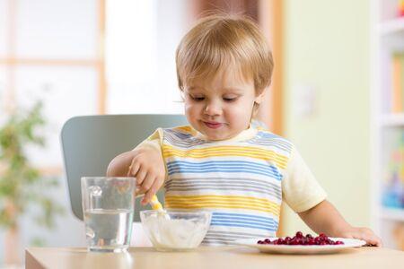 nursery: muchacho niño comer la comida con la cuchara en la sala de lactancia