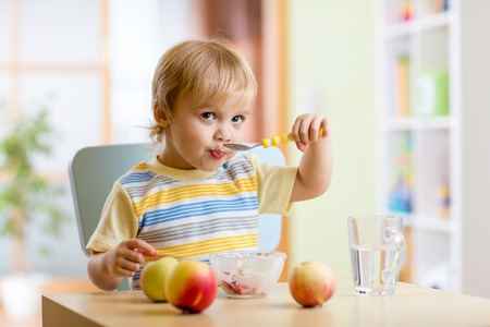 comiendo: Niño lindo que come el alimento sano con una cuchara en el hogar
