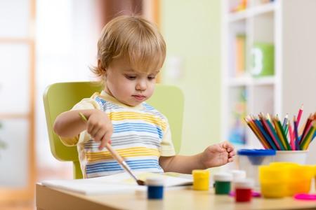 kinder: Feliz pintura del ni�o chico en clase creativa en el kinder Foto de archivo