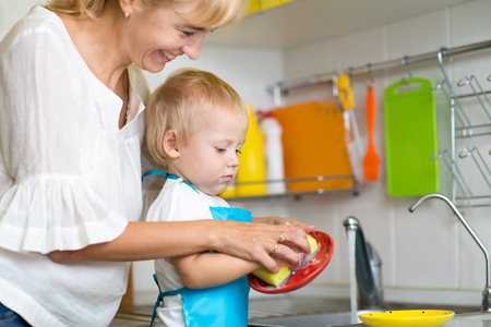 doing: Kid child and mother washing dishes - having fun together in the kitchen Stock Photo