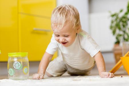 aliments: Ludique enfant gar�on avec ustensiles de cuisine et des denr�es alimentaires sur le sol dans la cuisine