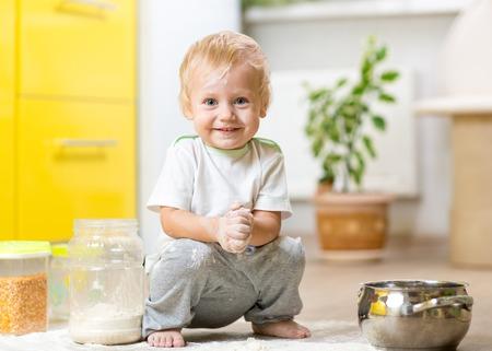 aliments: Ludique tout-petit enfant avec le visage sale farine. Petit gar�on entour� d'ustensiles de cuisine et des denr�es alimentaires