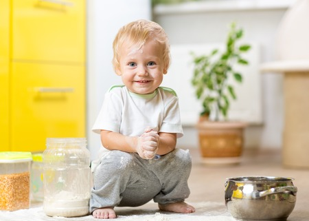 splotchy: Playful child toddler with face soiled flour. Little boy surrounded kitchenware and foodstuffs Stock Photo