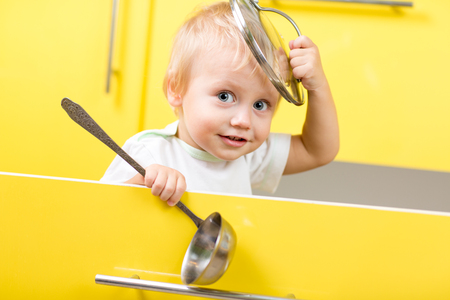 Grappig kind jongen zit in de gele open keuken doos met laddle