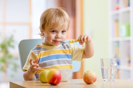 cuchara: Feliz niño pequeño niño que come el alimento de queso con frutas en el hogar