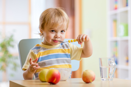 spoons: Happy child toddler eating food cheese with fruits at home