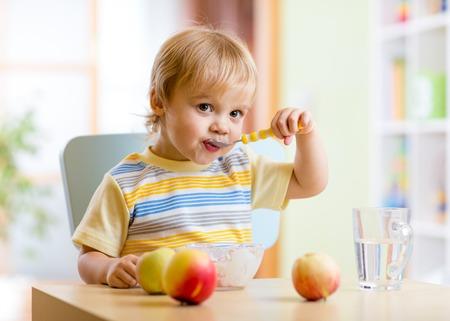 Leuk kind het eten van gezond voedsel met met de linkerhand thuis Stockfoto