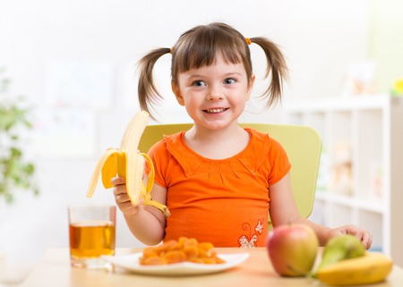 eating: Beautiful child girl eating healthy food fruits at home Stock Photo