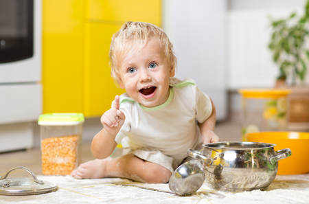foodstuff: Playful child boy with kitchenware and foodstuffs on floor in kitchen