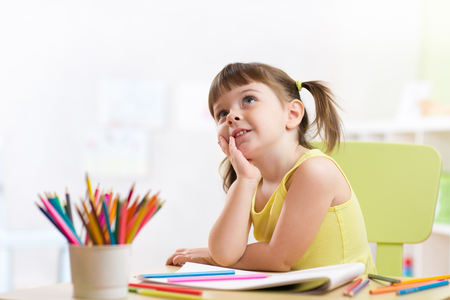 drawing room: Cute dreamy kid girl drawing with color pencils in nursery