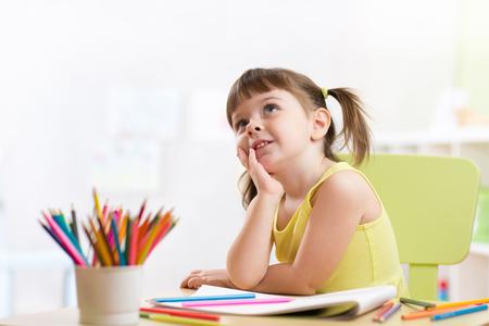nursery education: Cute dreamy kid girl drawing with color pencils in nursery
