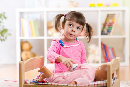 Child girl plays doctor examining baby doll patient with toy stethoscope