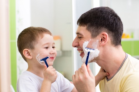 playful father and kid son shaving together at home bathroom photo