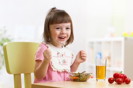 niños sentados: Niño que se sienta en la mesa de la comida lista para comer en la guardería. Ensalada vegetariana y verduras frescas para el almuerzo del niño.