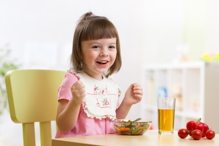 lunch table: Toddler sitting at table food ready to eat in the nursery. Vegetarian salad and fresh vegetables for child lunch.