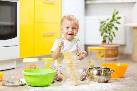 smeared baby: Playful kid toddler with face soiled flour. Little boy surrounded kitchenware and foodstuffs Stock Photo