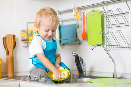 Cute child boy 2 years old washing up in kitchen