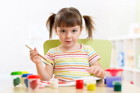 playschool: kid playing and painting at home or kindergarten or playschool Stock Photo