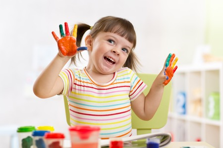 painted hands: Portrait of kid girl with painted hands at home