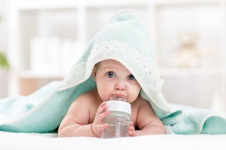 Adorable child baby drinking water from bottle. Little girl  wrapped bathing towel lying on bed. Stock Photo